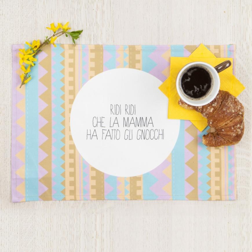 """""""Ridi ridi che la mamma ha fatto gli gnocchi"""" è uno dei soggetti delle tovagliette azteche di Carilllon Design, l'ingrediente giusto per iniziare un'ottima giornata!  Ispirate ai viaggi in Messico e alle Texture della moda, sono pillole del buon umore.  Le tovagliette riprendono le citazioni della nonna e lo può confermare Elisa Palmisano, ideatrice del marchio, che fin da piccola, con la sua famiglia, ne sentiva delle belle. Sono divertenti, cool, in un raffinatissimo gabardine di cotone 100% e sono tutte da gustare, a partire da una bella colazione."""